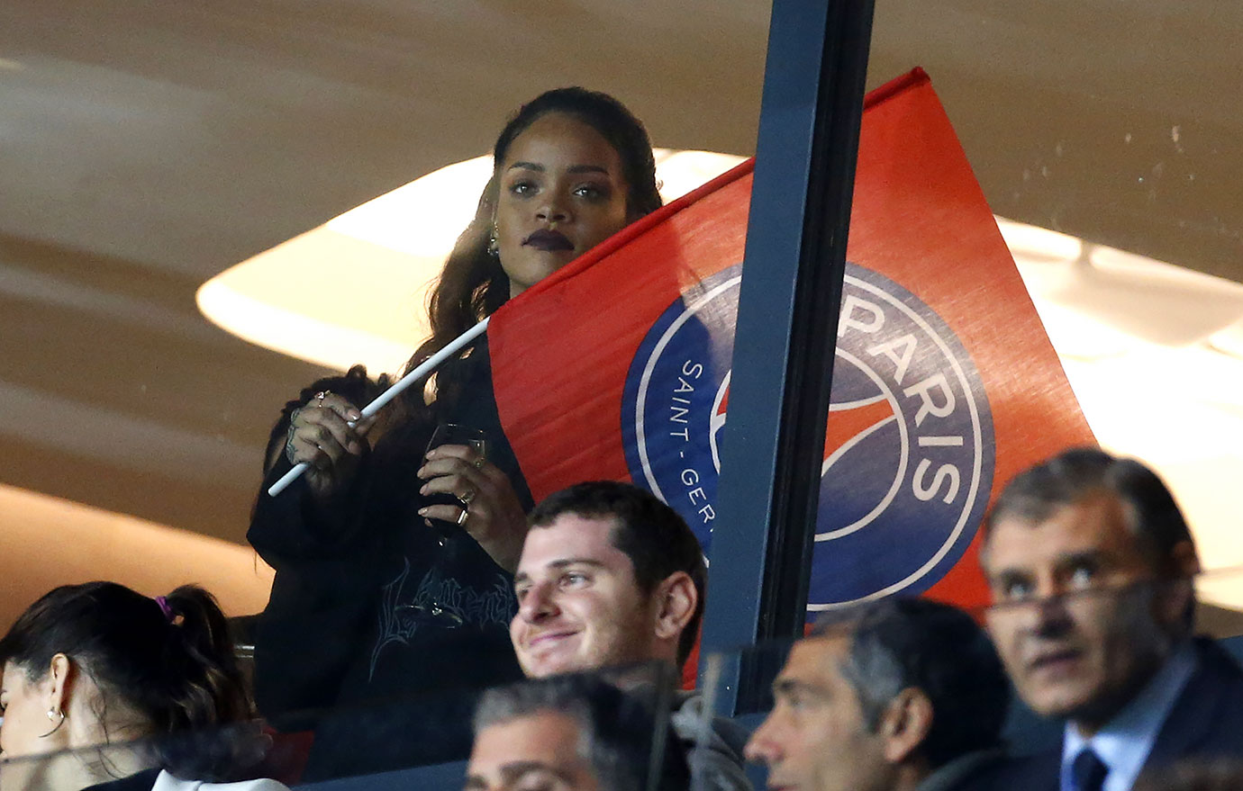 Rihanna waves a flag for Paris Saint-Germain FC (PSG) during their French Ligue 1 match against Olympique de Marseille at Parc des Princes stadium on Oct. 4, 2015 in Paris.