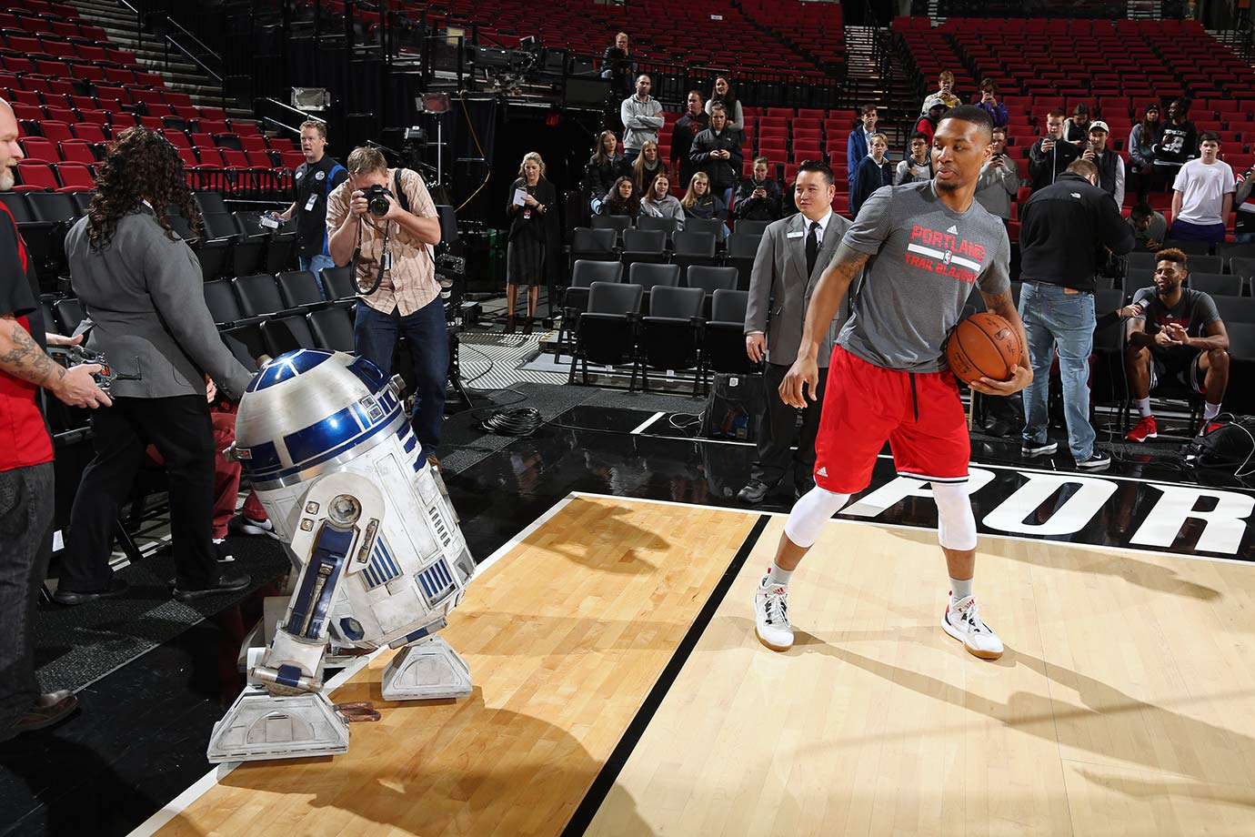 Portland Trail Blazers point guard Damian Lillard looks back at R2-D2 before a game against the New Orleans Pelicans on Dec. 14, 2015 at the Moda Center Arena in Portland, Ore.