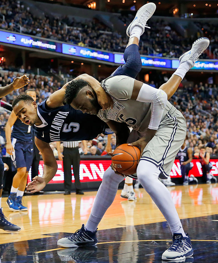 Villanova guard Phil Booth falls over Georgetown center Jessie Govan.