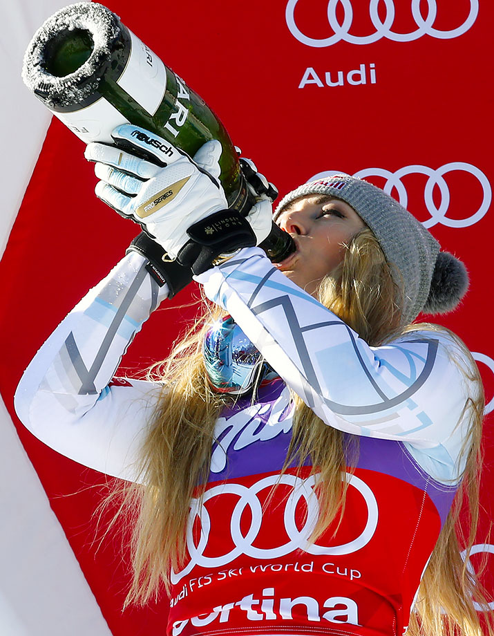 Lindsey Vonn chugs sparkling wine as she celebrates on the podium after setting a new record with her 37th career World Cup downhill win in Cortina D'Ampezzo, Italy.