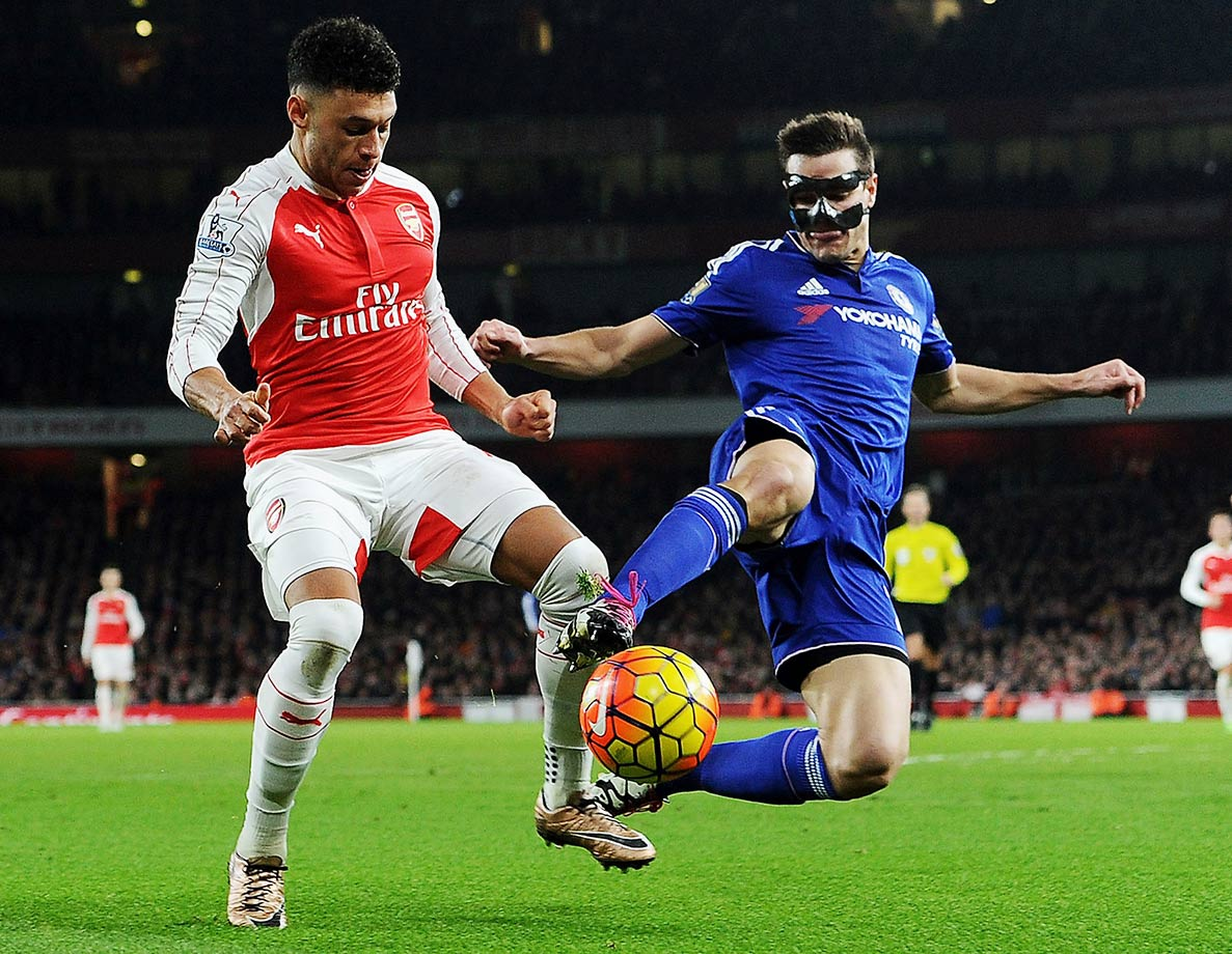 Arsenal's Alex Oxlade-Chamberlain takes on a masked-man, Chelsea's Cesar Azpilicueta, during the Barclays Premier League match at Emirates Stadium in London.