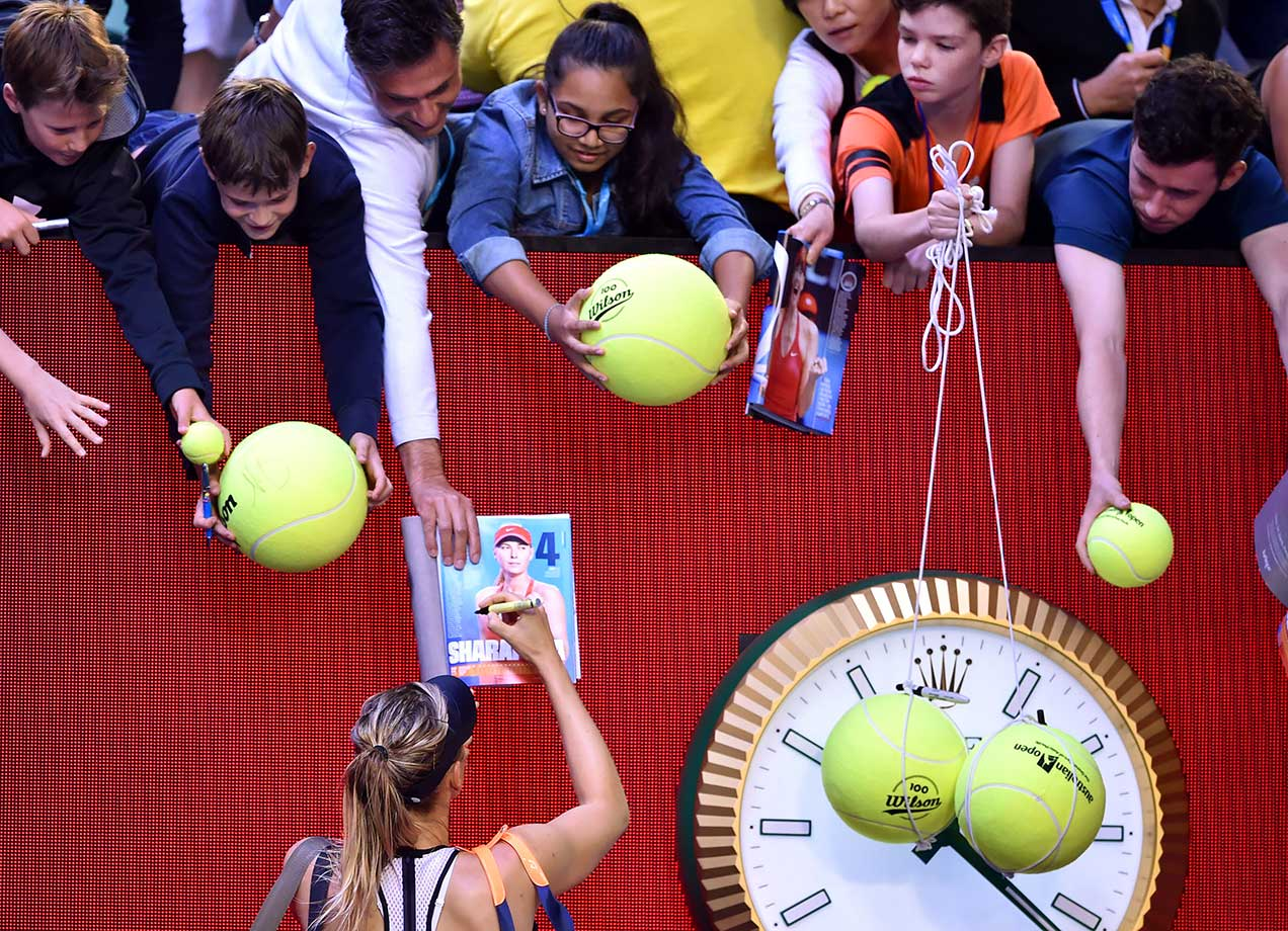 Maria Sharapova signs autographs as one young fan looks for her to sign his giant pair of tennis balls following her victory against Belinda Bencic at the Australian Open in Melbourne.