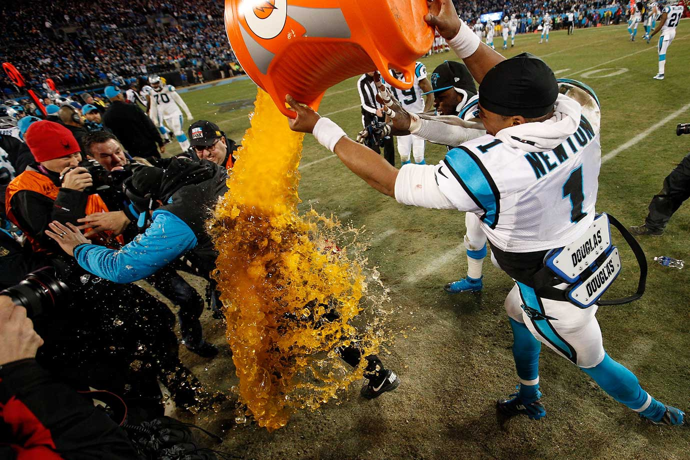 Carolina Panthers head coach Ron Rivera tries to evade a gatorade shower courtesy of Cam Newton and Charles Johnson following their NFC Championship Game victory over the Arizona Cardinals at Bank of America Stadium in Charlotte, N.C.