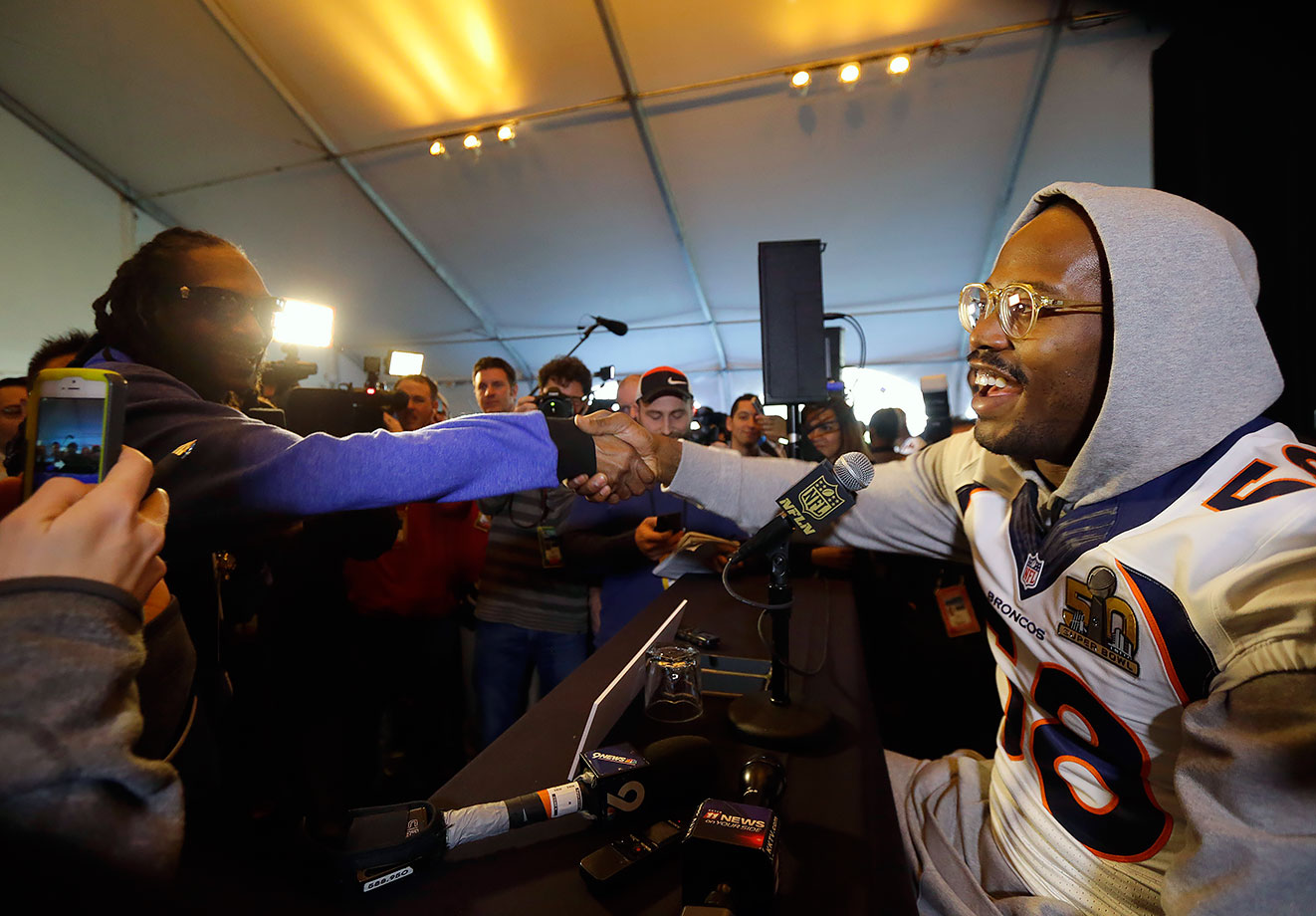 Von Miller is greeted by Snoop Dogg while speaking to reporters in Santa Clara, Calif.