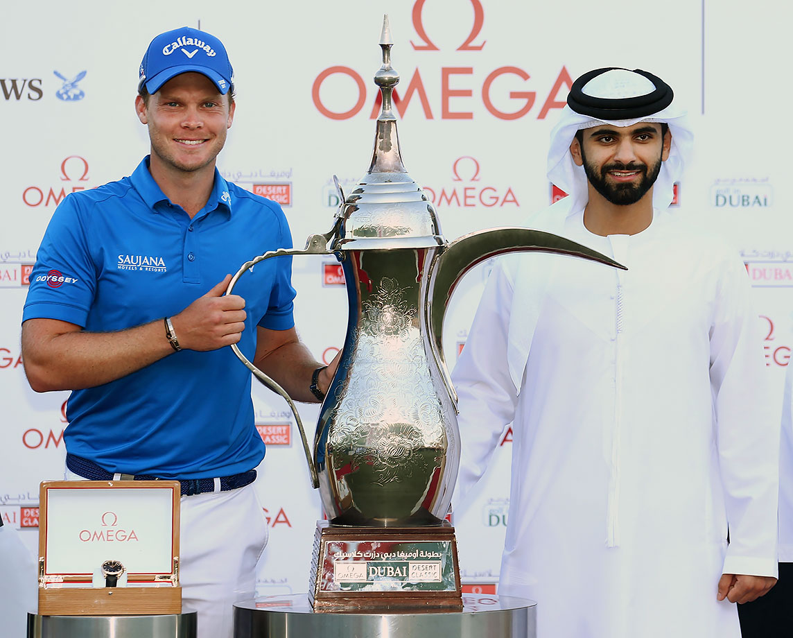 Danny Willett is presented with a trophy by Sheikh Mansoor bin Mohammed bin Rashid al-Maktoum after the final round of the Omega Dubai Desert Classic at the Emirates Golf Club in Dubai, United Arab Emirates.