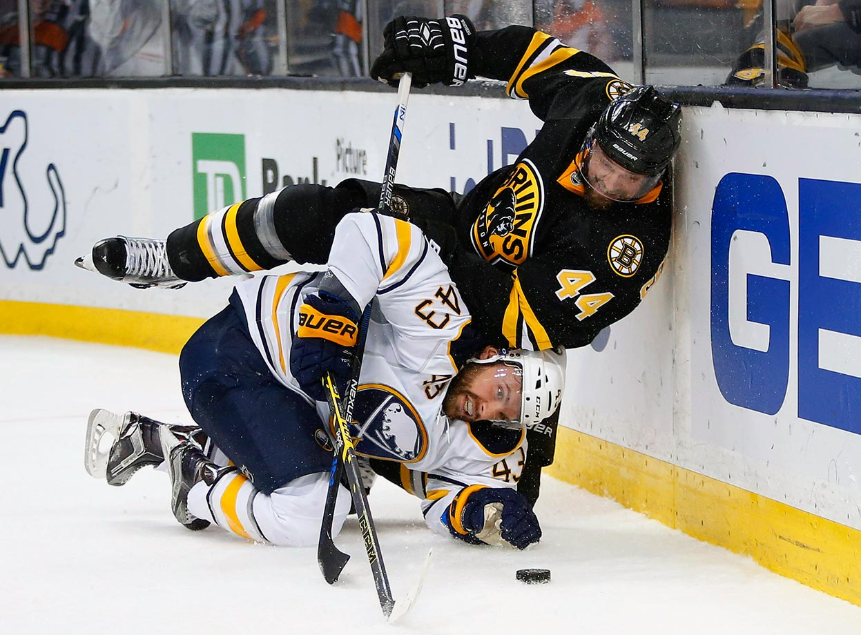 Dennis Seidenberg falls on Daniel Catenacci during a game between the Boston Bruins and Buffalo Sabres at TD Garden in Boston.