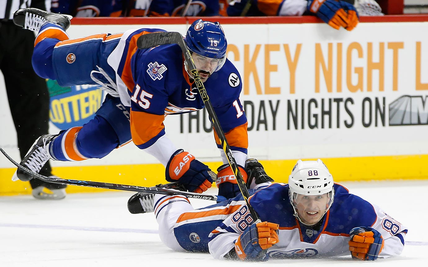 Cal Clutterbuck goes flying after tripping over Brandon Davidson during a game between the New York Islanders and Edmonton Oilers at Barclays Center in Brooklyn, N.Y.