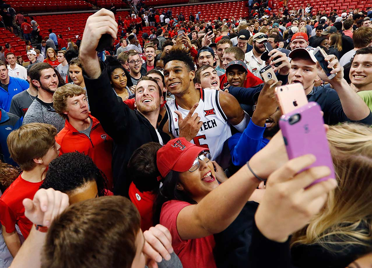 Texas Tech's Justin Gray poses for photos with fans after Tech defeated Iowa State 85-82 in overtime in Lubbock, Texas.