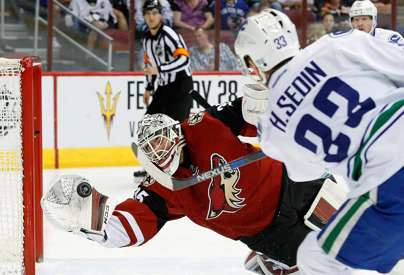 Louis Domingue makes a diving save on a shot by Henrik Sedin during the first period of the Arizona Coyotes game against the Vancouver Canucks in Glendale, Ariz.