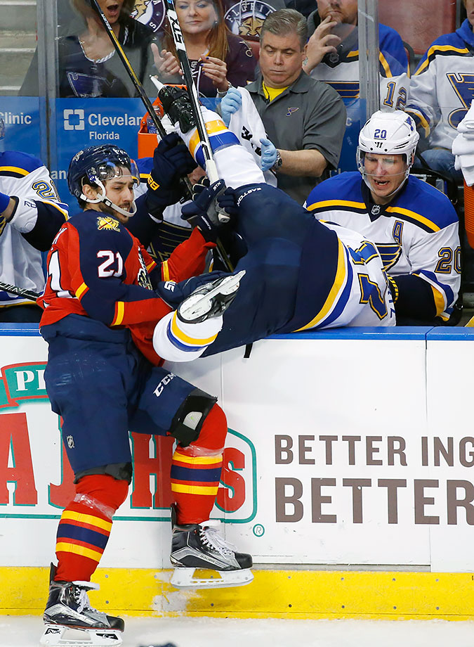 Vincent Trocheck shoves Jaden Schwartz over the boards and into the lap of his teammate Alexander Steen during the third period of the Florida Panthers game against the St. Louis Blues in Sunrise, Fla.