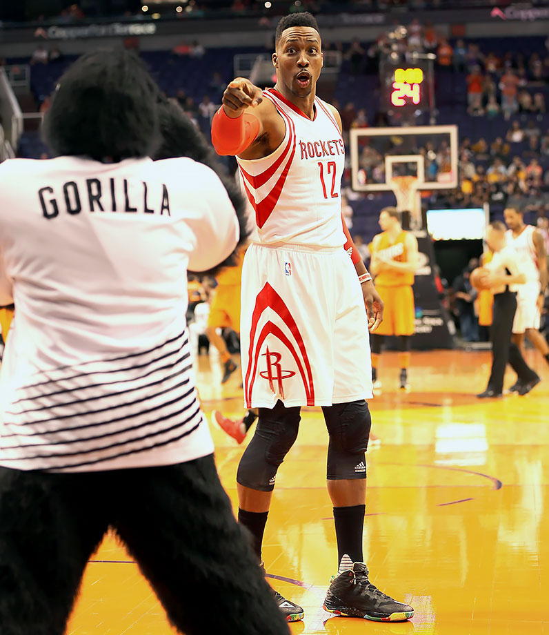 Houston Rockets center Dwight Howard jokes around with the Phoenix Suns Gorilla before a game in Phoenix, Ariz.