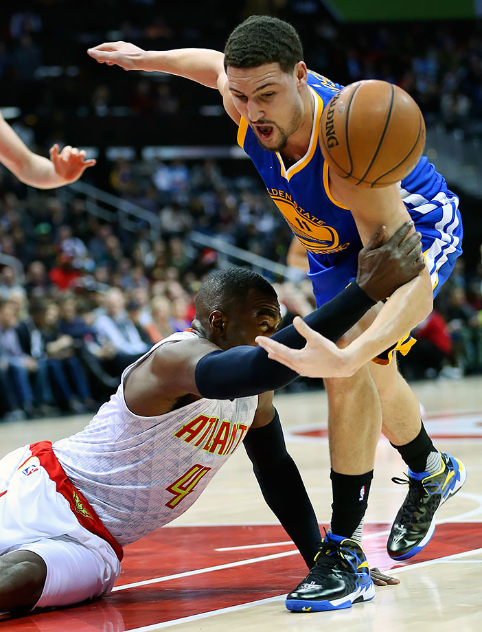 Atlanta Hawks forward Paul Millsap falls and grabs Golden State Warriors guard Klay Thompson in the first half of their game in Atlanta.