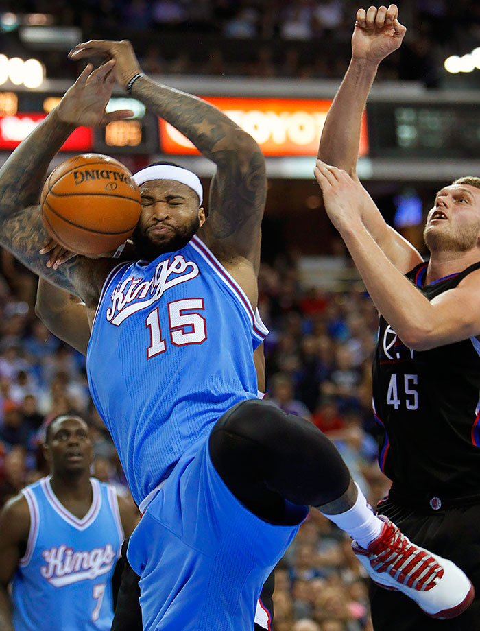 Sacramento Kings center DeMarcus Cousins is fouled under the basket by Los Angeles Clippers center Cole Aldrich during the second half of a game in Sacramento, Calif.