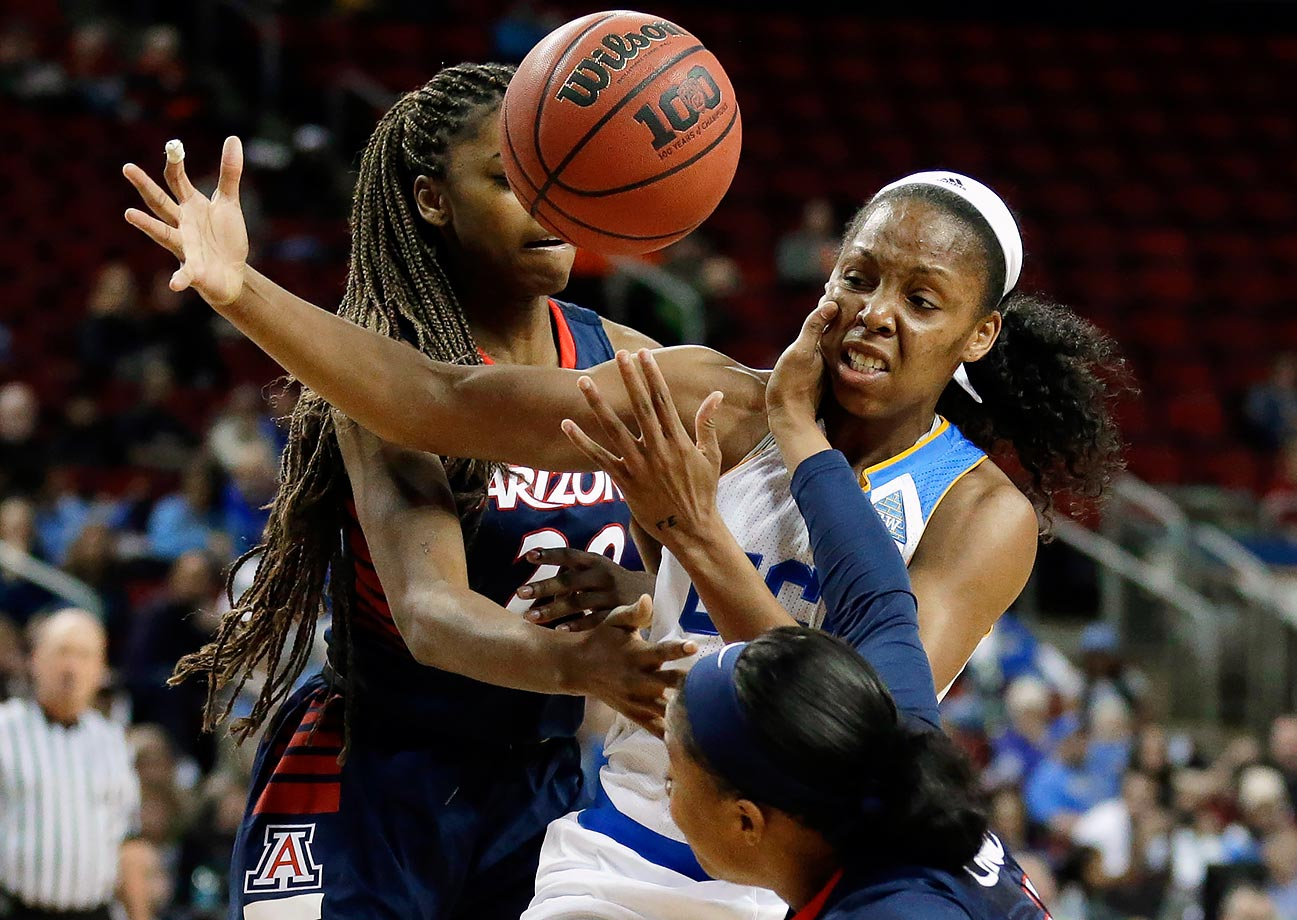 UCLA's Nirra Fields battles with Arizona's Farrin Bell and Keyahndra Cannon for the ball during the first half of a Pac-12 Conference tournament game in Seattle.