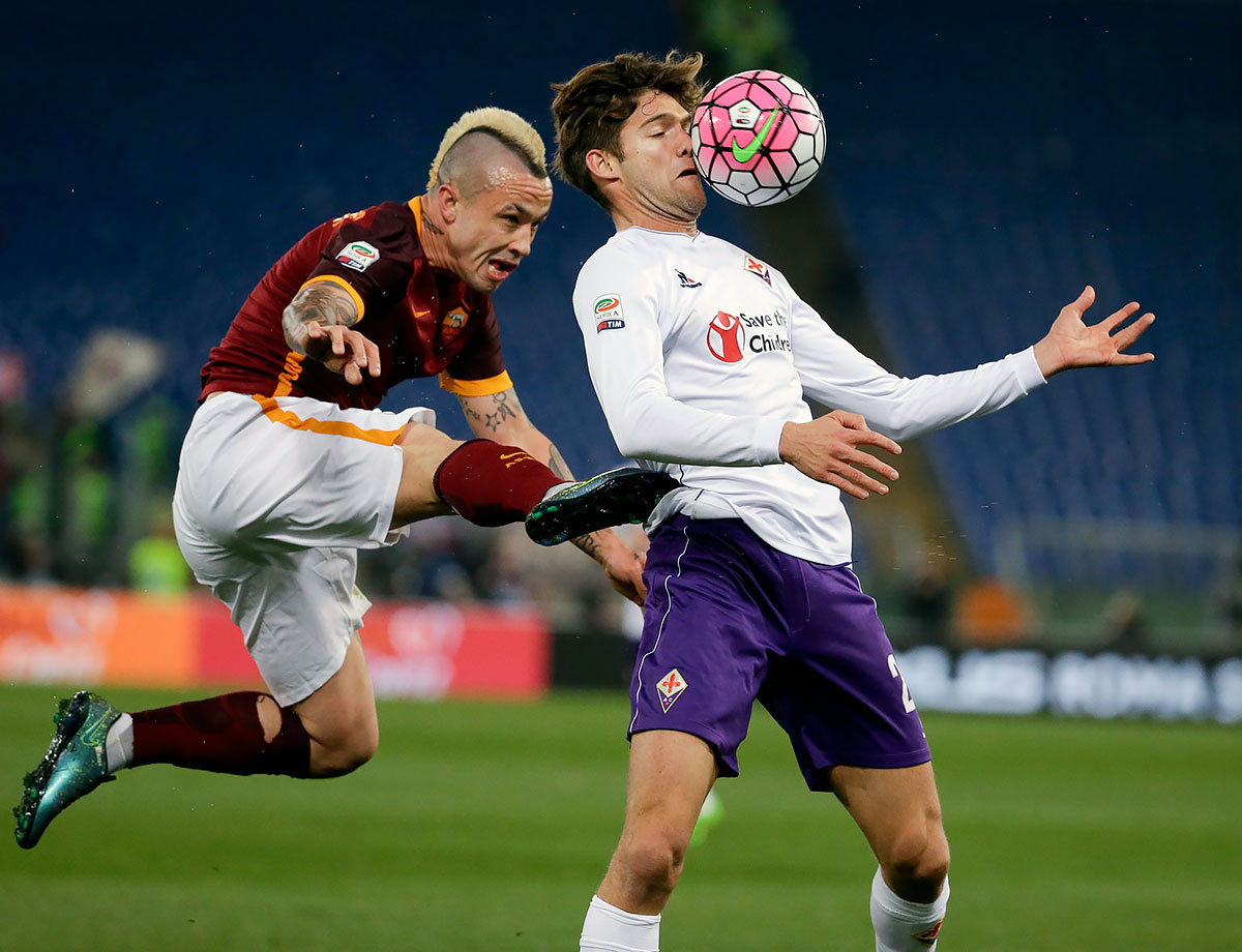 Roma's Radja Nainggolan and Fiorentina's Mendoza Marcos Alonso vie for the ball during a Serie A match at Rome's Olympic stadium.