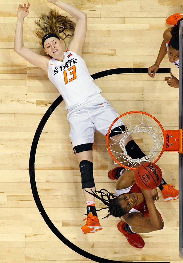 Oklahoma State's Jentry Holt falls to the floor as Oklahoma's Vionise Pierre-Louis shoots in the first half of a Big 12 Conference tournament game in Oklahoma City,