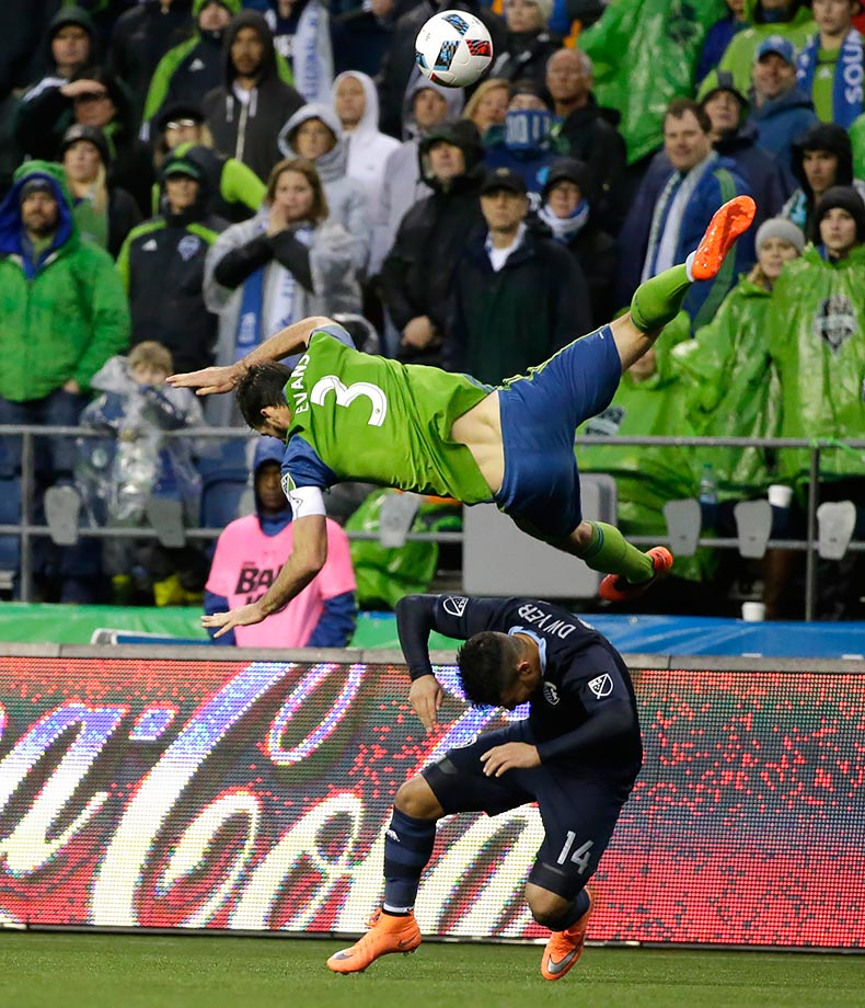 Seattle Sounders defender Brad Evans falls over Sporting Kansas City forward Dom Dwyer after Evans went up for a header in the second half of a match in Seattle.