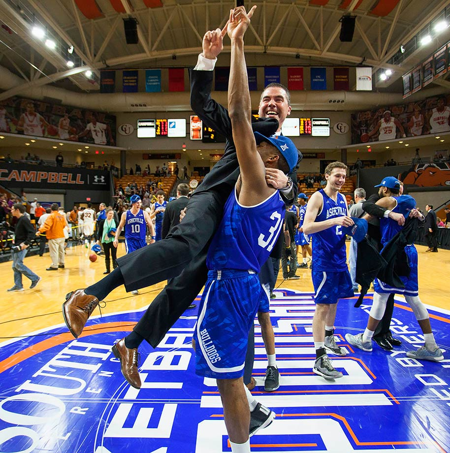 UNC Asheville's Sam Hughes lifts coach Nick McDevitt into the air after winning the Big South Conference tournament championship game in Buies Creek, N.C.