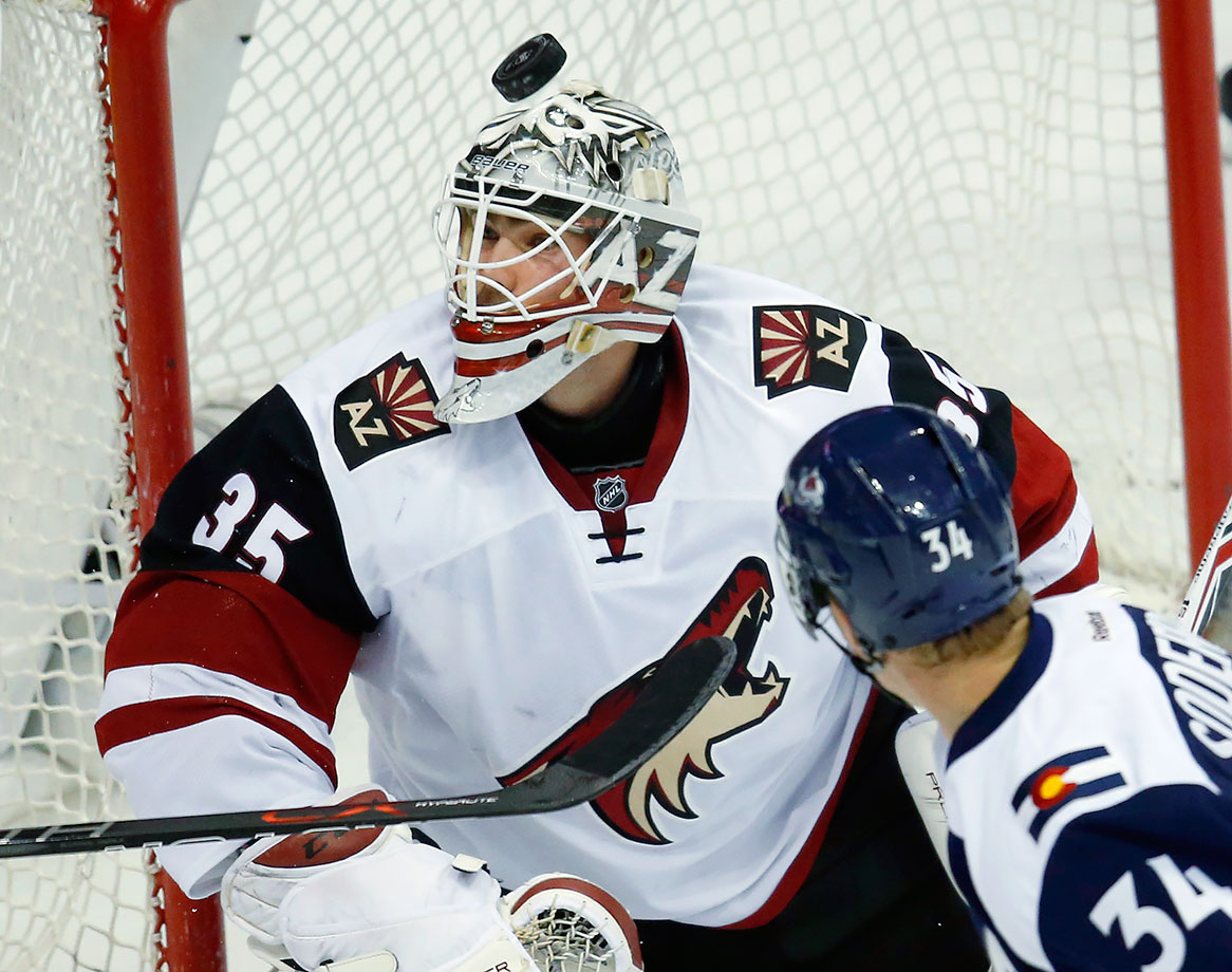 Arizona Coyotes goalie Louis Domingue has the puck fly over his head after stopping a shot off the stick of Colorado Avalanche center Carl Soderberg in the first period of a game in Denver.