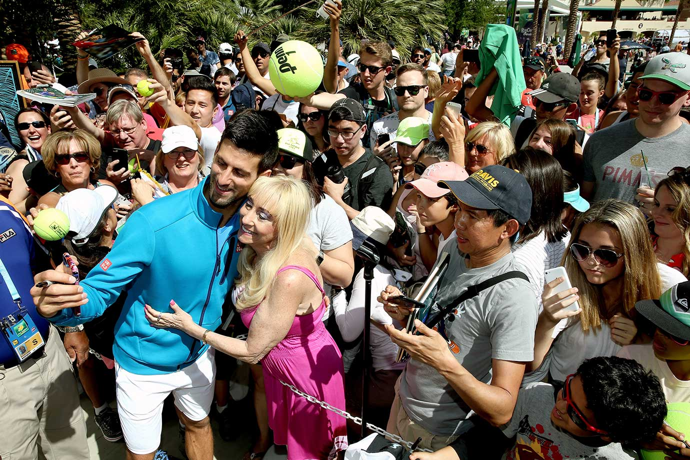 Novak Djokovic poses for a selfie with a fan as he signs autographs during the BNP Paribas Open in Indian Wells, Calif.