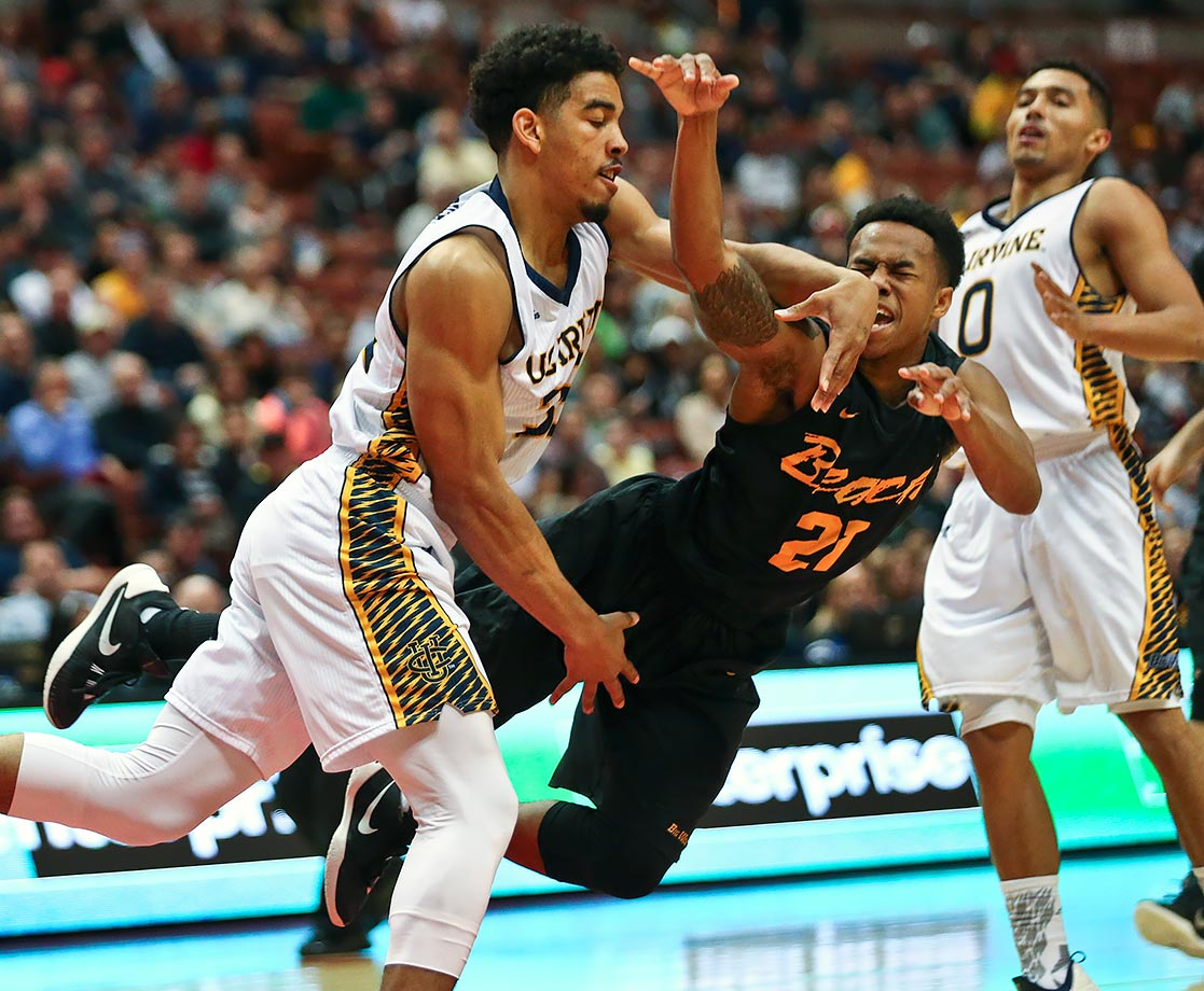 Long Beach State guard Justin Bibbins is knocked to the floor after shooting by UC Irvine guard Aaron Wright during the first half their Big West Conference Tournament game in Anaheim, Calif.