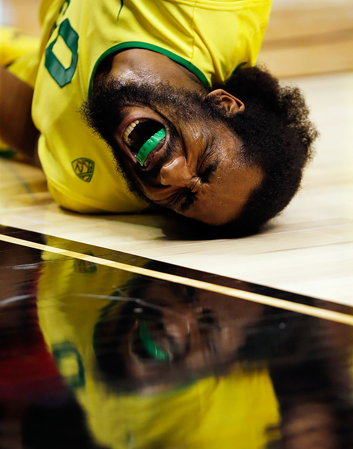 Oregon forward Dwayne Benjamin writhes in pain on the court after a play against Arizona during the second half of their Pac-12 Tournament game in Las Vegas.