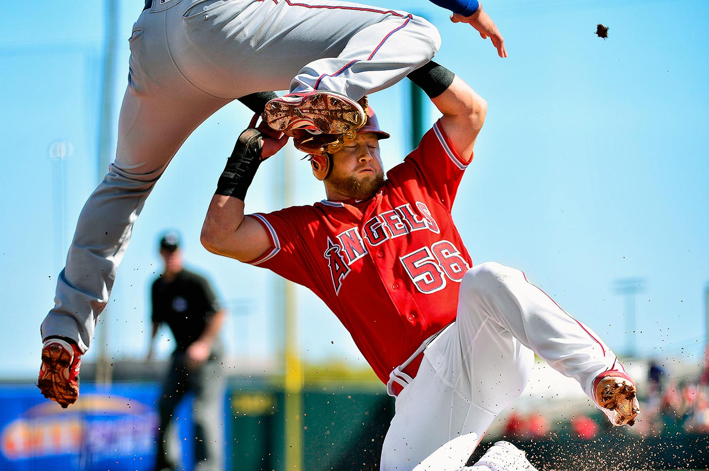 Los Angeles Angels baserunner Kole Calhoun safely slides under Texas Rangers third baseman Joey Gallo in the second inning of their spring training game in Tempe, Ariz.