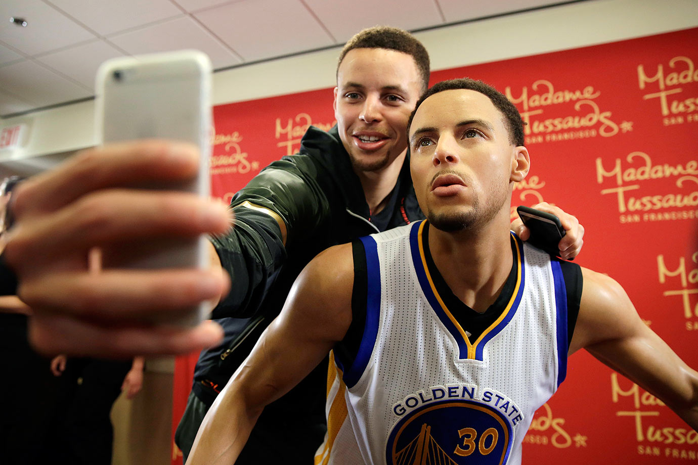 Golden State Warriors guard Stephen Curry takes a selfie with his wax figure by Madame Tussauds after its unveiling in Oakland, Calif.