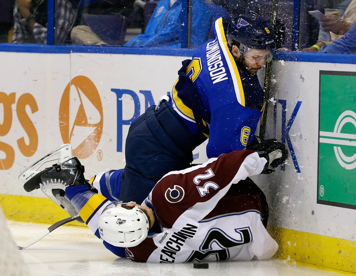 St. Louis Blues defenseman Joel Edmundson and Colorado Avalanche defenseman Francois Beauchemin slam into the boards while chasing the puck during the second period of their game in St. Louis.