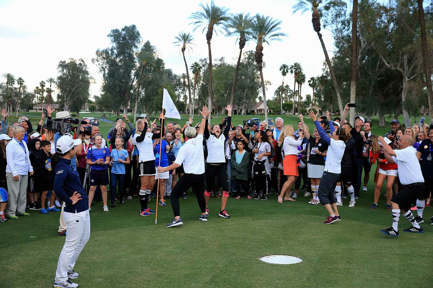 Paula Creamer celebrates with Abby Wambach and other players as her 'foot putt' goes into the hole during the ANA Footgolf Faceoff between Team USA and Team Japan as a preview for the ANA Inspiration at the Mission Hills Country Club in Rancho Mirage, Calif.