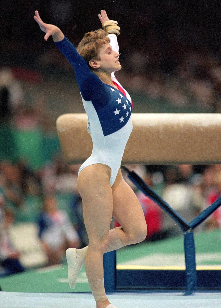 Atlanta Olympics, July 23, 1996 | Kerri Strug holds her pose after sticking the landing on her vault despite a painful ankle injury suffered on her first attempt. The United States' gold medal hopes rested on her, and she fought the pain on her second attempt to secure the title for the U.S.