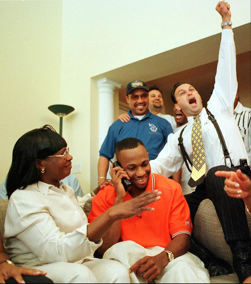 University of Miami defensive back Duane Starks, with his mother seated next to him, smiles as he is informed of being drafted 10th by the Baltimore Ravens in 1998.