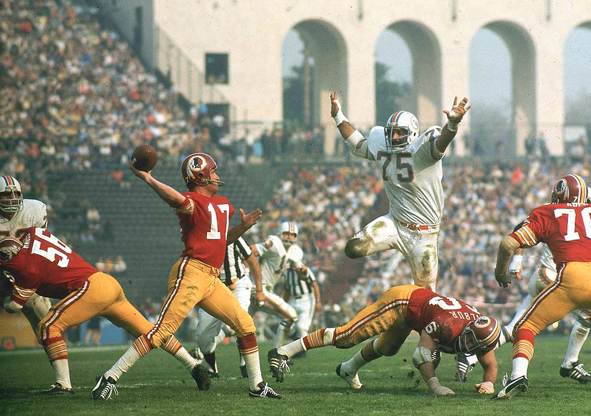Super Bowl VII, Jan. 14, 1973 | Dolphins defensive lineman Manny Fernandez (75) hurdles a Redskins offensive lineman in pursuit of quarterback Billy Kilmer (17). Fernandez would finish the game with 17 tackles as the Dolphins defeated the Redskins 14-7 to become the first and last team to finish an NFL season undefeated.