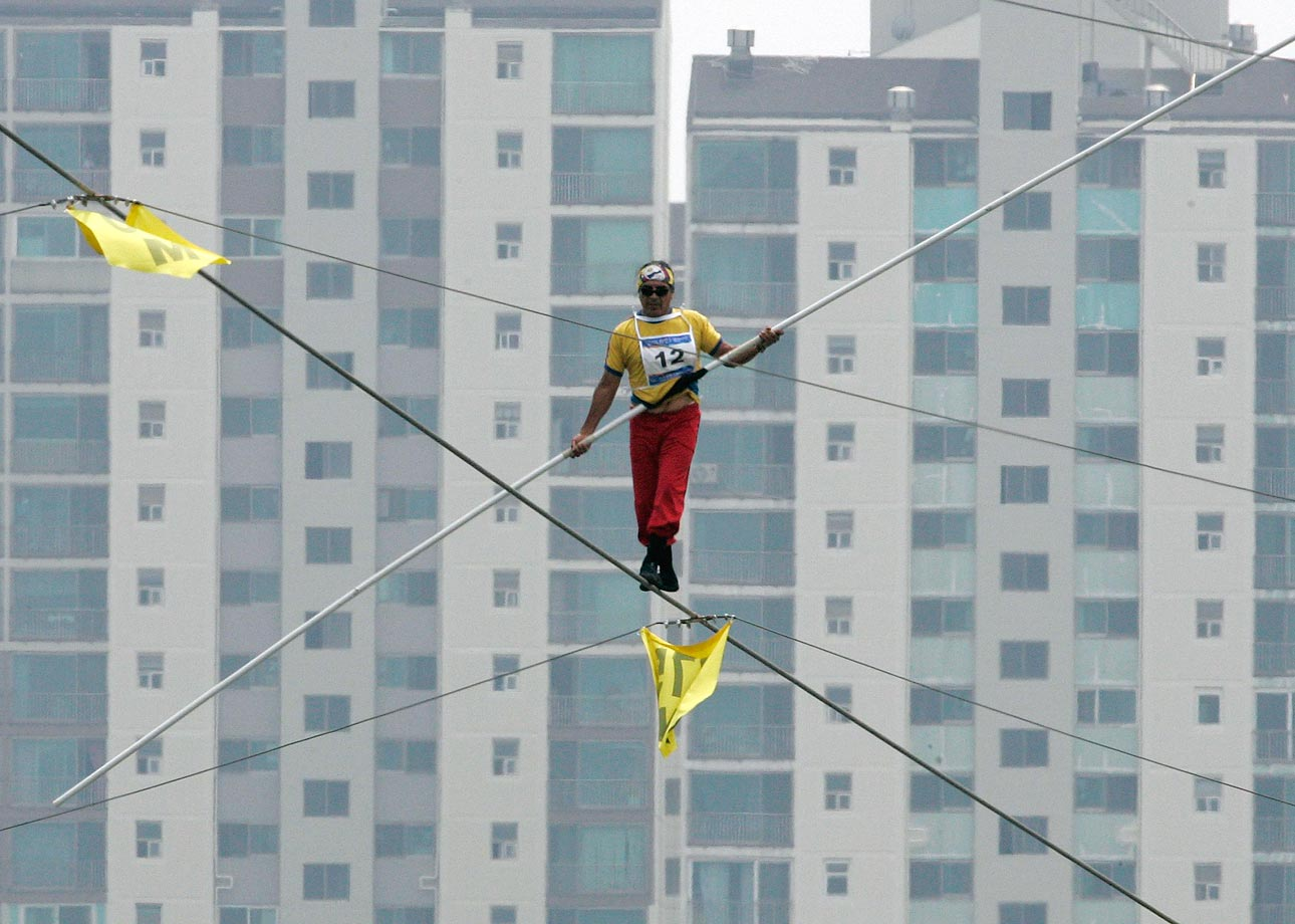 "Jorge Arturo Ojeda of Ecuador competes during the speed race of the 2009 Hangang High Wire World Championship in Seoul, in which participants cross the Han River on a 1 km (0.62 miles) wire. Twenty high-wire walkers from 12 countries participated in the event, which is part of the annual ""Hi Seoul Festival"" organized by Seoul City."