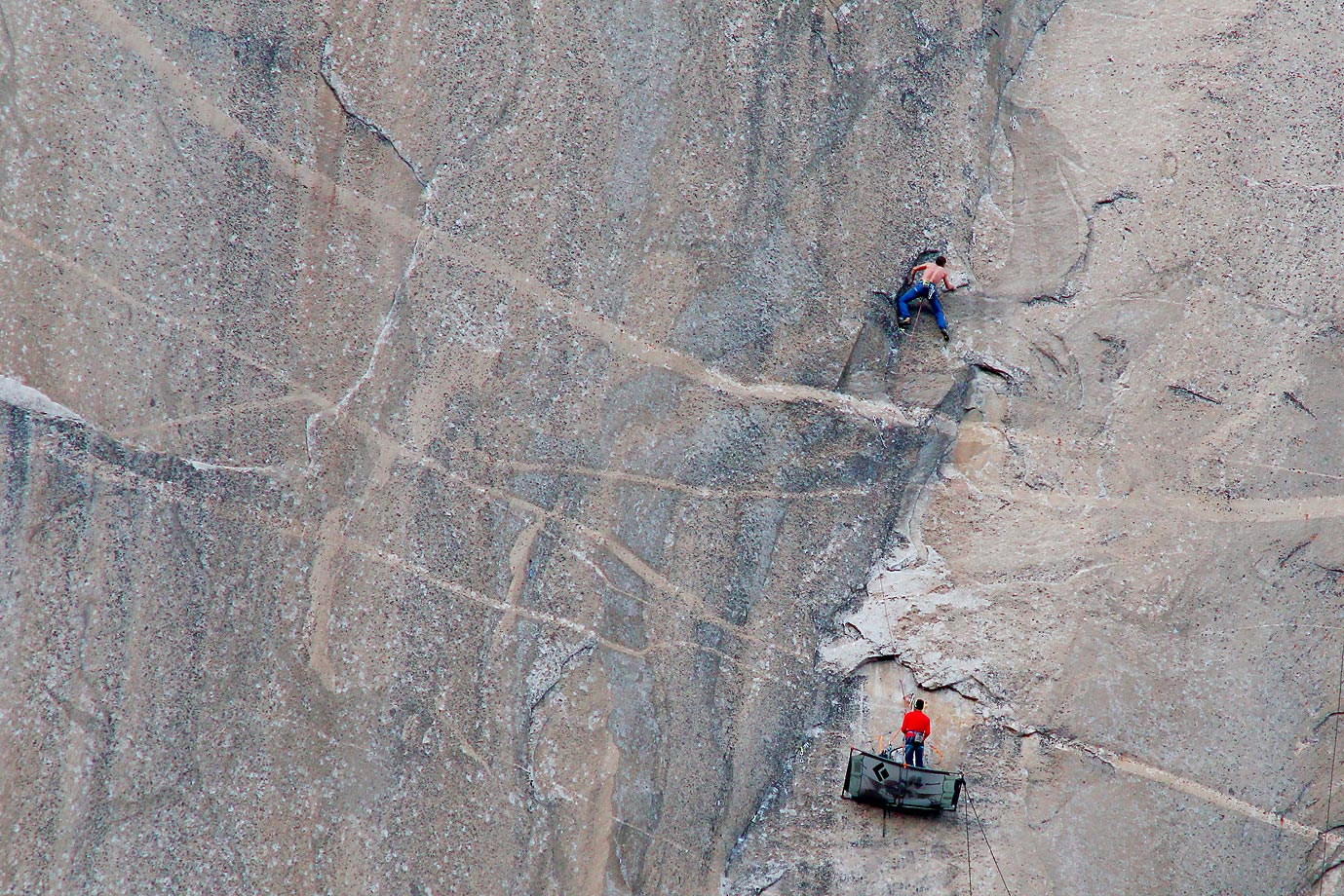 Tommy Caldwell (shirtless) climbing Pitch 17 and Kevin Jorgeson (in red) is belaying.