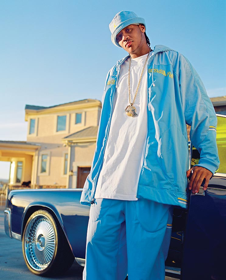Carmelo Anthony sporting his old Denver Nuggets colors and leaning against the side of his blue car.