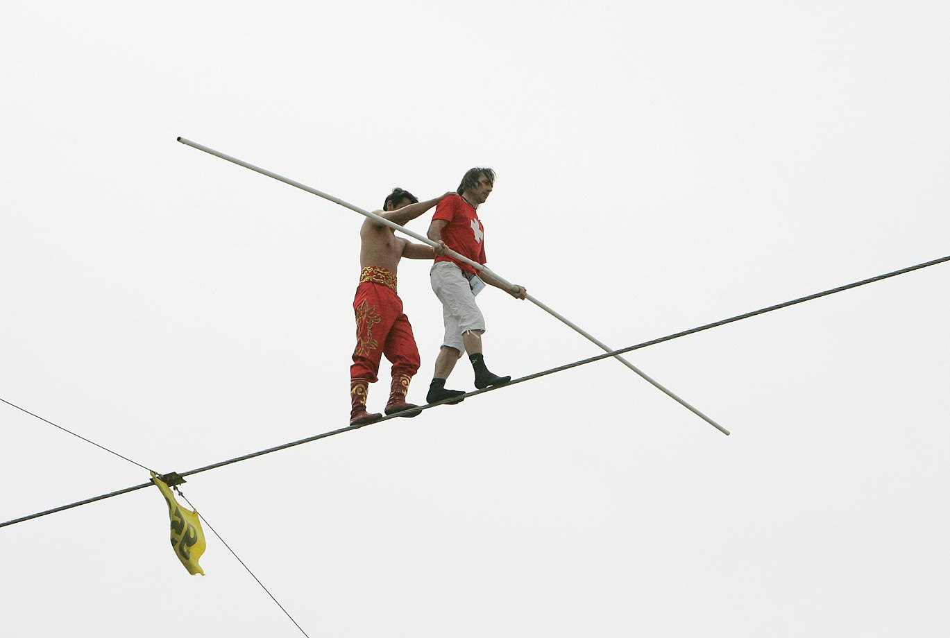 Alfred Nock Junior (right) of Switzerland helps Ya Kefujiang Maimitili of China after Ya dropped his bar during the speed race of the 2009 Hangang High Wire World Championship.