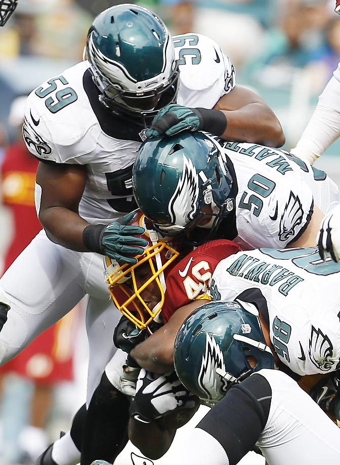 Washington Redskins running back Alfred Morris is tackled by Philadelphia Eagles linebackers Connor Barwin, Casey Matthews and DeMeco Ryans.