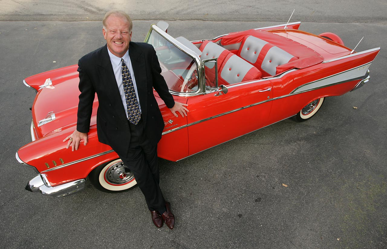 Kent Benson standing by his flashy red convertible in 2006.