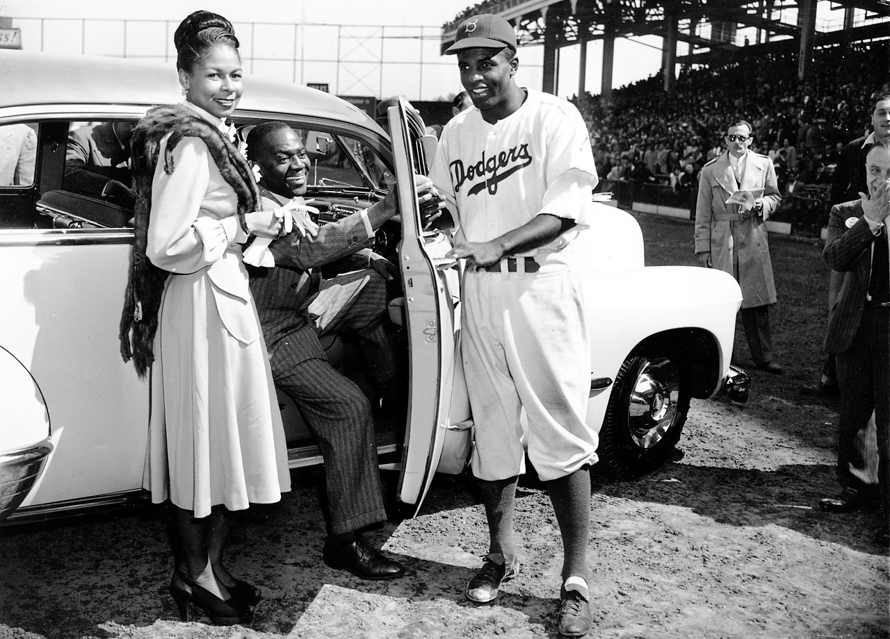 "Jackie Robinson is handed the keys to this car by tap dancer Bill Bojangles Robinson in 1947.  The car was an award presented to Robinson by fans on ""Jackie Robinson Day"" at Ebbets Field."