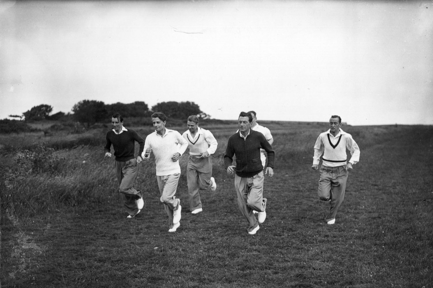 British tennis players Fred Perry and Dan Maskell, along with other members of the 1936 Davis Cup team, being trained on Beachy Head, Eastbourne, by the Arsenal football club coach Tom Whittaker.