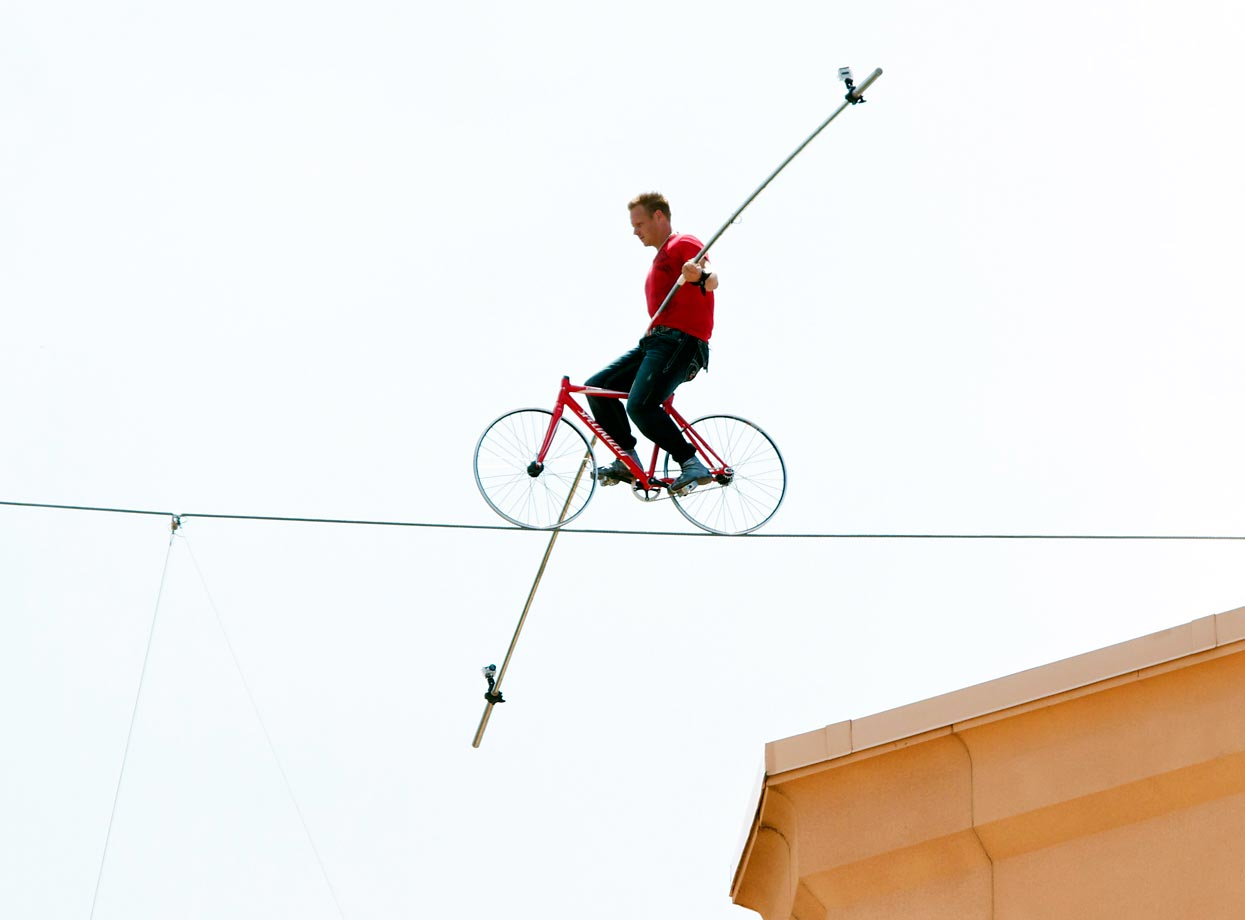 Nik Wallenda impressively and safely pedals a bicycle more than 100 feet across the Bridge Suite of the Paradise Island Atlantis resort in Nassau, the Bahamas. Wallenda, of the famous Flying Wallendas circus family, cycled along the wire some 260 feet above the ocean without a safety net to break his own Guinness World Record.