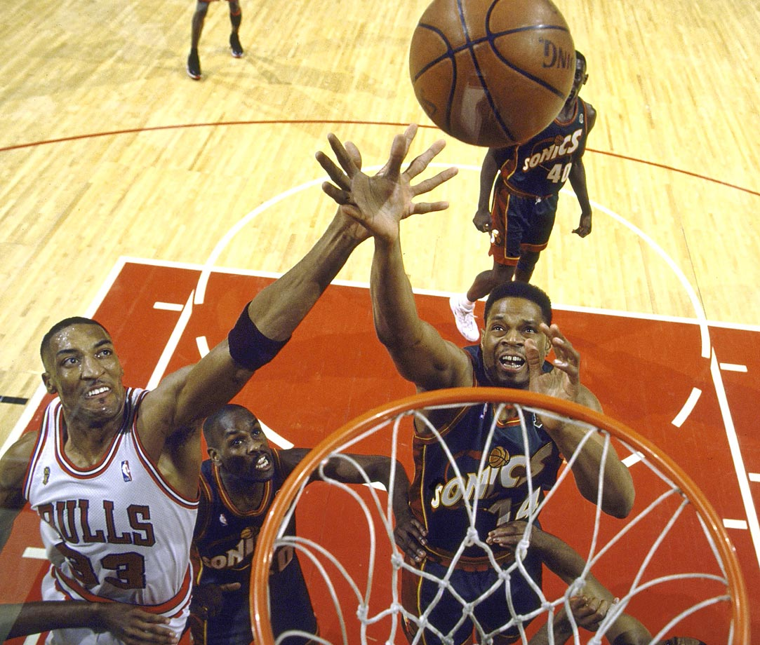 Scottie Pippen of the Bulls and Sam Perkins of the Sonics battle for a rebound. Pippen led Chicago in assists on the series, and the Bulls took their fourth championship, emboldened by Jordan's return from a two-year retirement.
