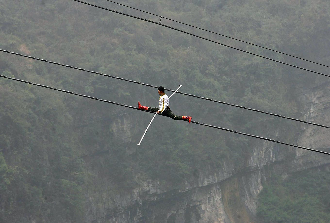 Saimaiti Aishan, the seventh-generation Dawazi high wire stuntman from China, challenges the Tianmenshan Mountain cableway in Zhangjiajie, China. Unfortunately, the steepest section of the cable defeated Aishan, and he could not complete his walk.