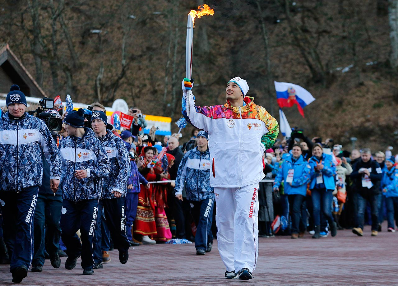 Former Olympic bob sleigher Alexey Voyevoda of Russia carries the Olympic torch in the mountain village of Krasnaya Polyana, Russia, ahead of the Sochi 2014 Winter Olympics.