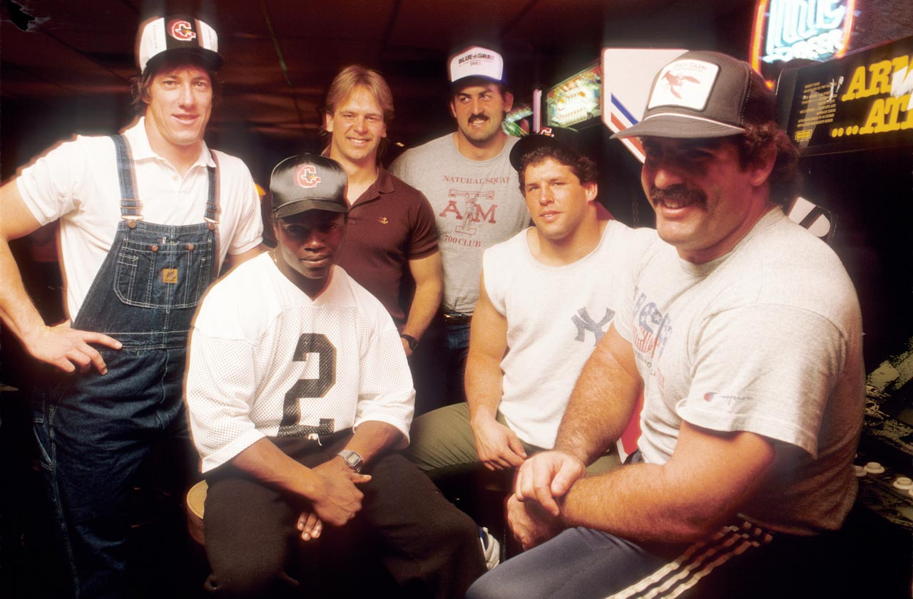 Despite being known for his no-huddle offense, Houston Gamblers quarterback Jim Kelly huddles around with his teammates in a Huntsville, Texas bar. Kelly would go on to play in four Super Bowls with the Buffalo Bills over 11 seasons in the NFL.