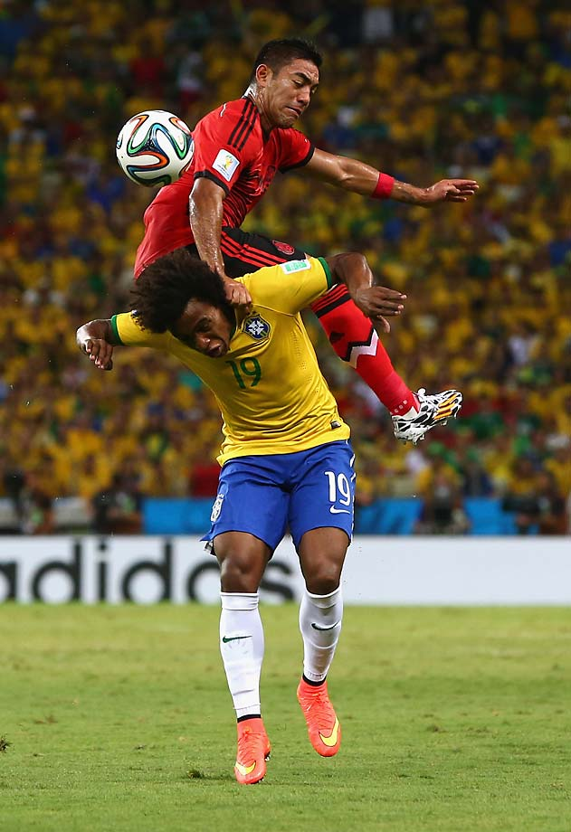Marco Fabian of Mexico challenges Willian of Brazil resulting in a foul against the Mexican player.