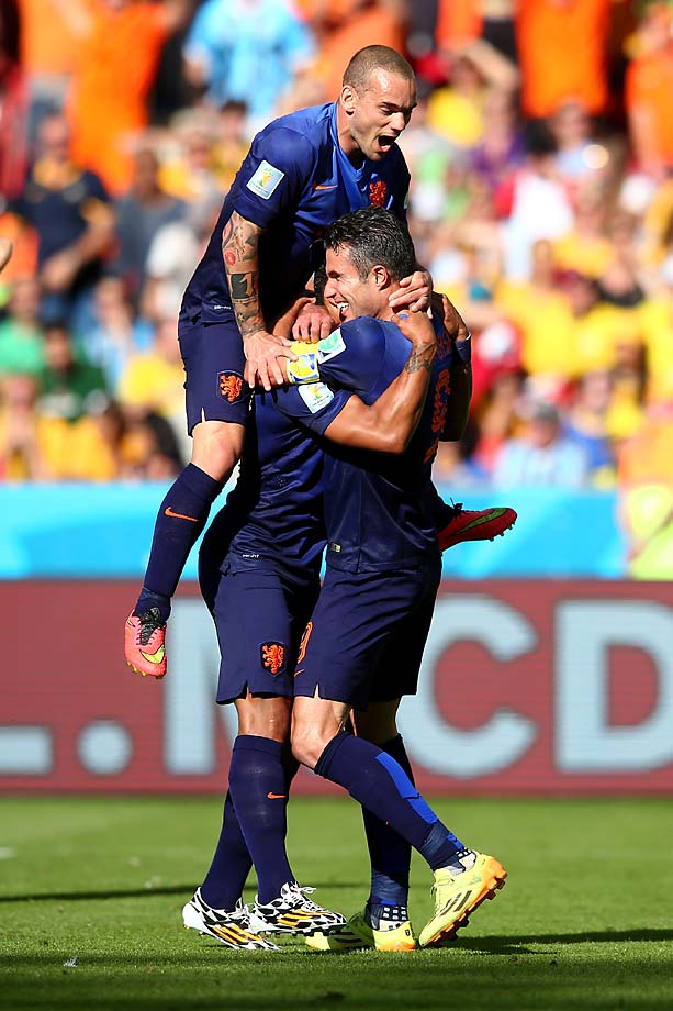 Memphis Depay of the Netherlands jumps into teammates' arms in celebration after scoring the team's third goal in the group B match.