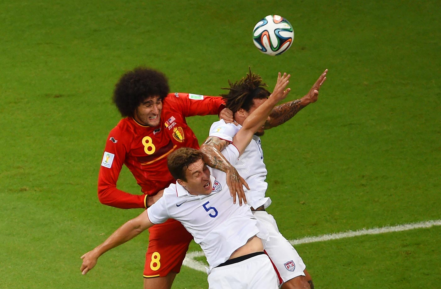 American teammates Matt Besler and Jermaine Jones challenge Belgium midfielder Marouane Fellaini in the first half.