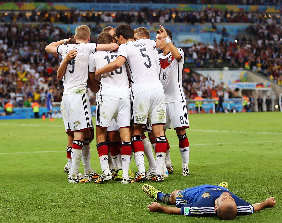 Argentine midfielder Javier Mascherano lies on his back as members of the German national team celebrate their victory in the World Cup Final at the Maracanã in Rio de Janeiro, Brazil.